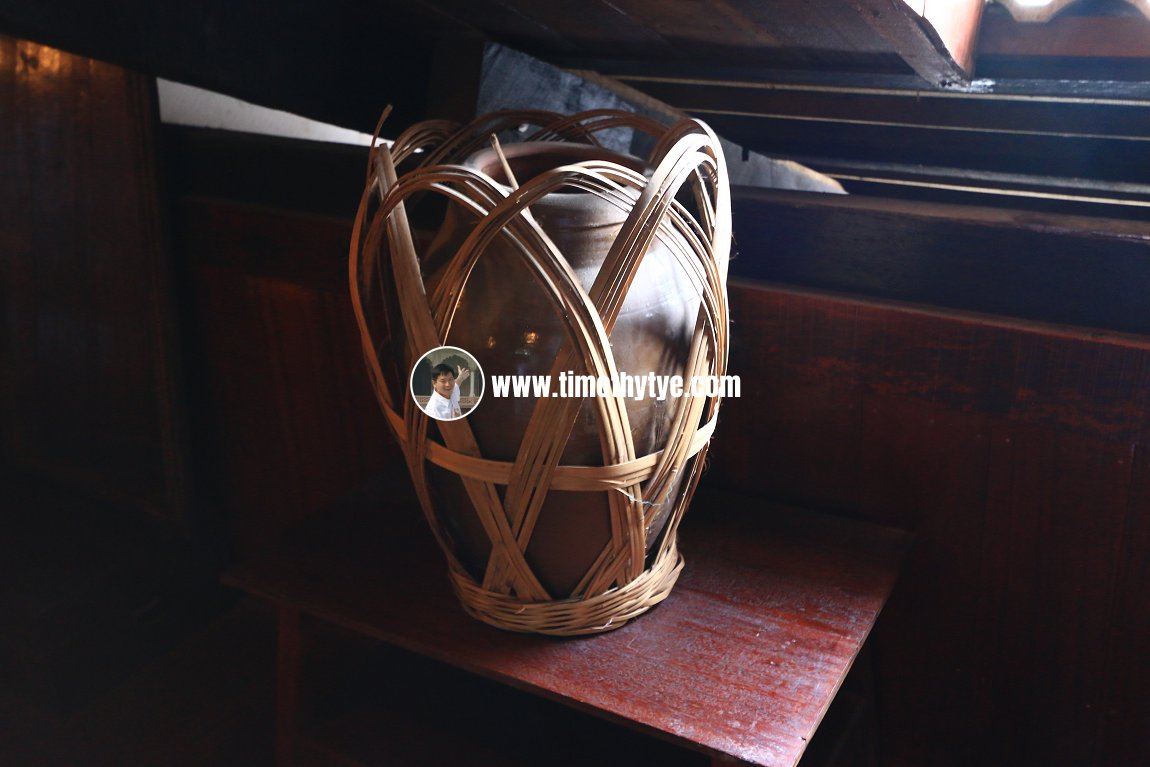 Water vessel with rattan carrier case.